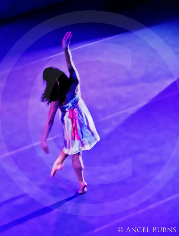 Footloose and Fancy Free, a dancer steps and swirls down an unseen path in lavender light, with arms raised